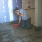 Jennifer Blumer on the phone while grouting